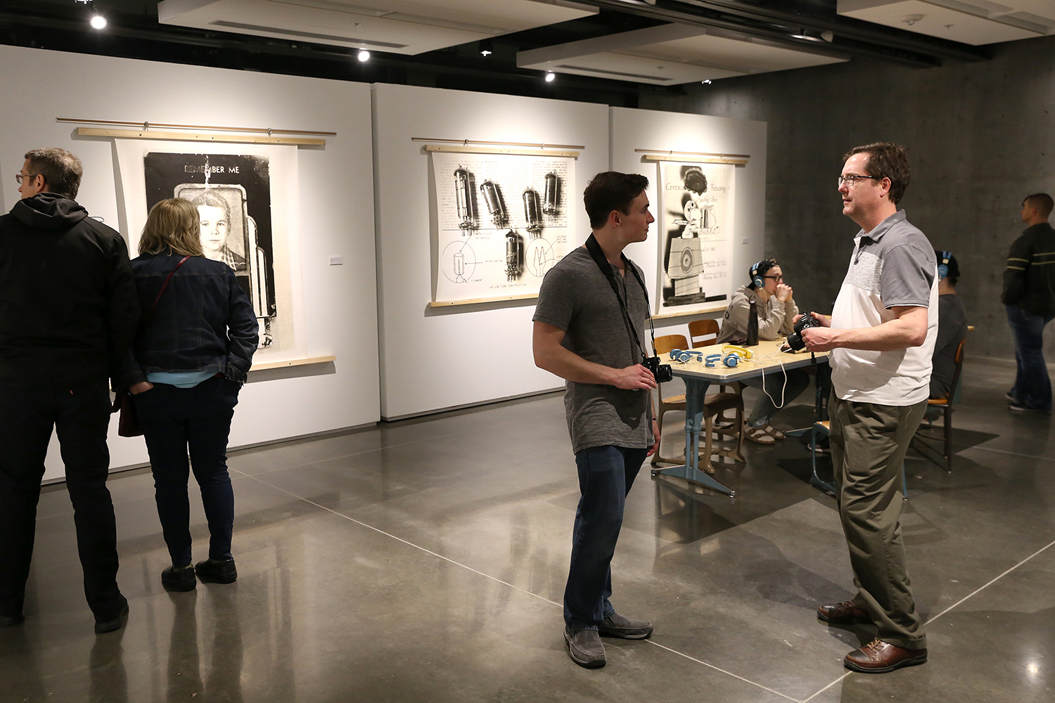 The artist talking with a viewer during the opening reception.