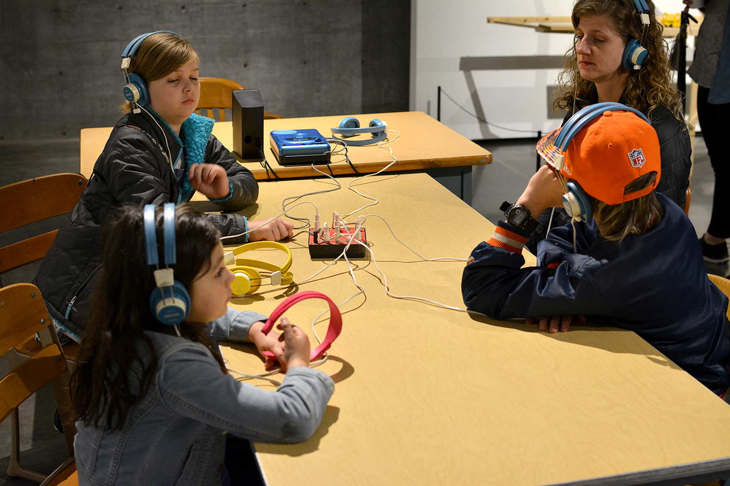 A mother and her three kids listening to the oral history recording at the main listening station.