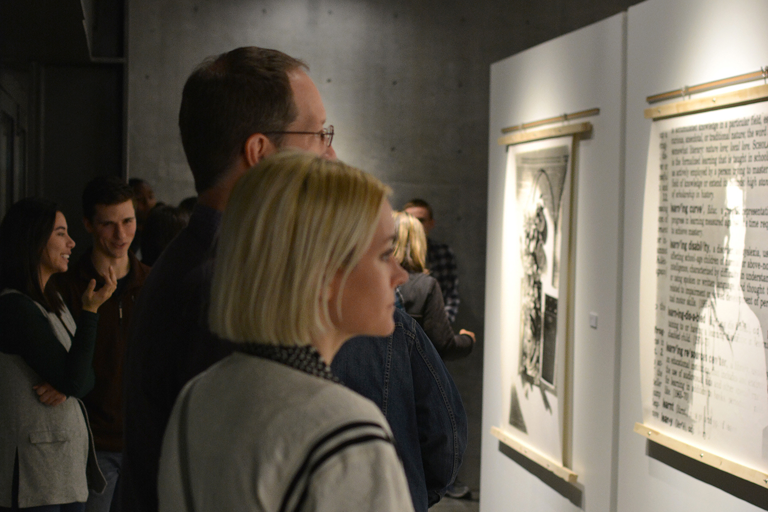 Poeple looking at the large scale gelatin silver prints.