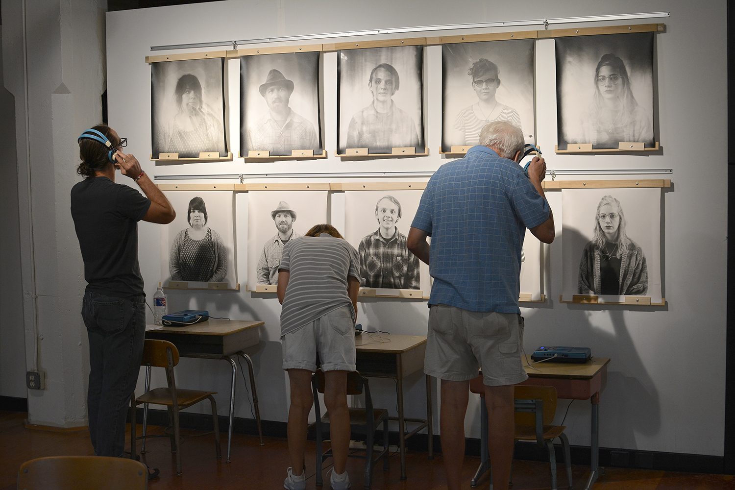 A group of people looking at the portraits and another group listening to a oral history recording.