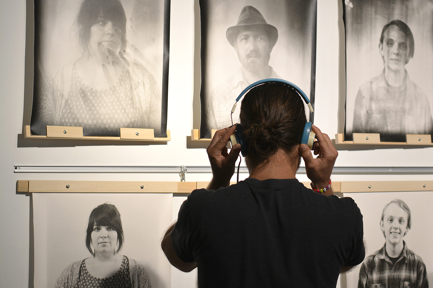 A person spends some time looking at the portraits and listening to a oral history recording.