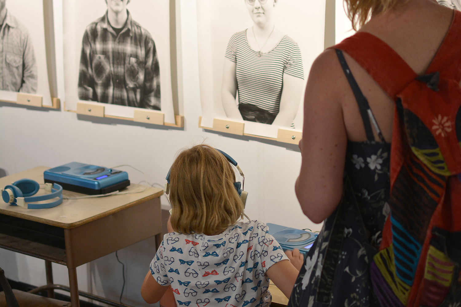 A mother and her kid listening to the oral history recording at a low listening station.